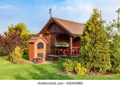 Landscaped summer garden with barbecue and wooden summerhouse. Green trees, flowerbeds, mown grass.