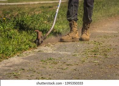 Landscaper using edger to edge sidewalk