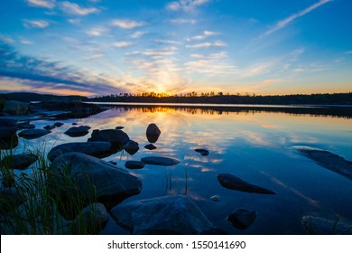 Landscapes of Finland. Summer sunset over the lake. Wildlife of the North. Coast. Northern nature of Finland. Traveling in Finland. Northern Europe. Suomi. Grass near the shore.