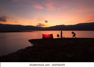 landscapes tent in the sunset near the lake with two silhouette of people.