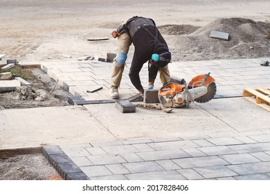 Landscaping contractor worker cutting and laying paving stones on residential driveway of a landscaping interlock construction site. Home renovation and improvement work business industry background.