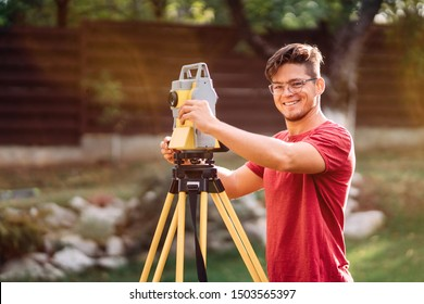 landscaping details - survey engineer in garden elevation using and working with theodolite