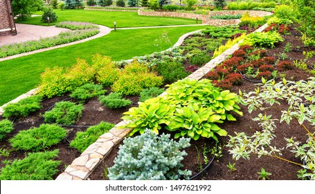 Landscaping panorama of home garden. Beautiful view of landscaped garden in backyard. Nice scenery of natural landscaping area in summer. Landscape design with plants and flowers at residential house.