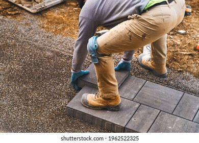 Landscaping paver worker laying paving stones on sandy ground of construction patio yard site in spring summer. Contractor wearing safety protective cloth, gloves and knee pads for installation work.