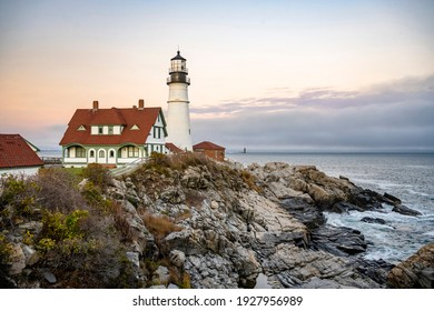 Landscaping of Silent Northeast Atlantic Ocean coast with skyline at low tide with rocks washed up by the surf and real operating Lighthouse at the top of the cliff showing the ships a safe way to go