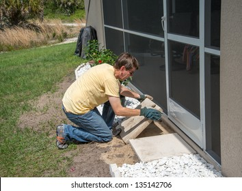 Landscaping Work - A man working outdoors.  He is placing heavy concrete patio slabs in the landscaping near the back door to the house.