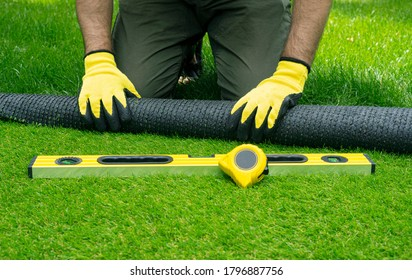 Landscaping of the yard with artificial turf. Gardener hands hold a roll of artificial grass.