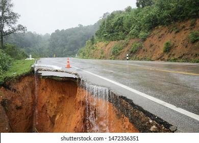 landslide caused by torrential rains occurs broken road asphalt. Broken cement on street. Cracked road from landslid destroyed by heavy rain