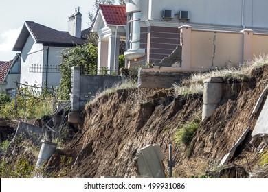 Landslide caused by torrential rains of Hurricane CHRISTIE. Broken road asphalt cracked and shifted after earthquake. Destroyed homes cottages large cracks, chips ranges cover large shift of mail