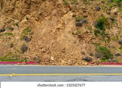 Landslide debris on rural road from steep slope after winter rain storm. Scattered pieces of rockslide debris cover red curb on highway.