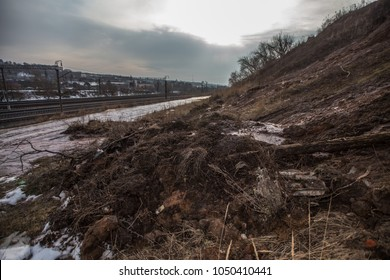 a landslide and pile of dirty earth came down from a hillside into a ravine in the spring