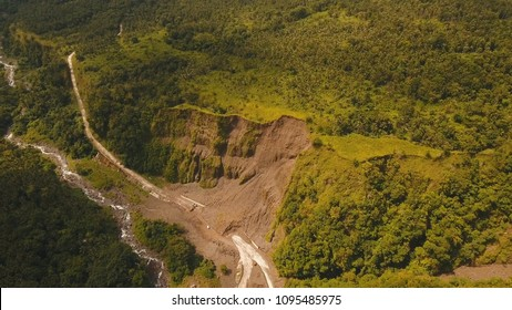 Landslides and rockfalls on the road in the mountains, Camiguin. Aerial view: mud and rocks blocking the road. Destroyed rural road landslide damaged in powerful flood. Collapsed on the mountain
