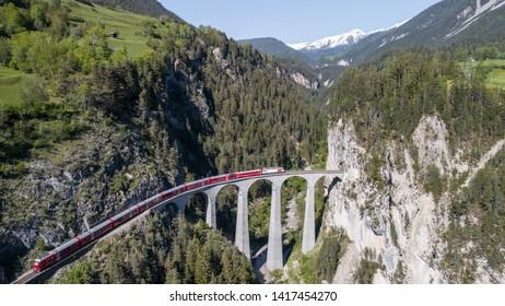 Landwasser viaduct, red train of Bernina  on the railway. Unesco World Heritage. Filisur, May 2019