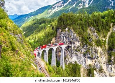 Landwasser Viaduct in summer, Filisur, Switzerland. It is landmark of Swiss Alps. Nice Alpine landscape. Red train of Bernina Express on railroad bridge in mountains. Panoramic view of famous railway. - Shutterstock ID 1619246908