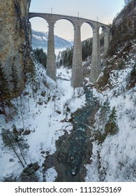 Landwasser Viaduct Switzerland Filisur Graubünden aerial view in Winter with mountains in background and creek