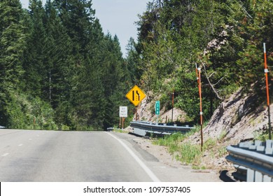 Lane merging sign on highway in old growth forest area. Montana, USA.