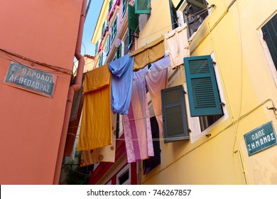 """The lane in the Old town of Corfu. On the walls signs with the street names - """"Zononos Street"""" and  """"6 lane St. Theodore"""". The dark green shutters are open.  Colored clothes drying on a clothesline."""