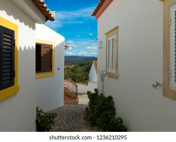 """lane in a village between houses with a view to the mountain landscape in """"Salir"""", Algarve, Portugal"""