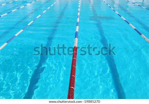 Lanes of sport swimming pool with turquoise water. Swimming pool with a lot od space for text. Swimmingpool lane markers. Swimming pool of olimpic type is ready for competition. Swimming pool surface.