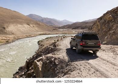 Langar, Tajikistan, August 23 2018: Off-road car is waiting on the Pamir Highway on the Pamir River. On the left of the river is Afghanistan and on the right Tajikistan