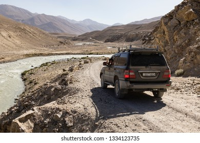 Langar, Tajikistan, August 23 2018: Off-road car is waiting on the Pamir Highway on the Pamir River. On the left of the river is Afghanistan and on the right Tajikistan