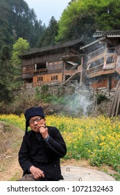 Langde, China - March 27, 2018: Miao man smoking a pipe in Langde Miao village, Guizhou province, China