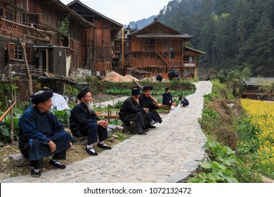 Langde, China - March 27, 2018: Old Miao men chatting in Langde Miao village, Guizhou province, China