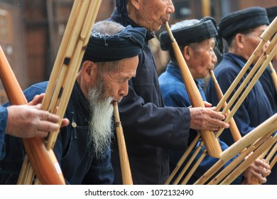 Langde, China - March 27, 2018: Miao men playing a traditional flute in Langde Miao village, Guizhou province, China
