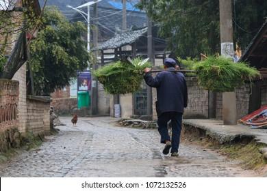 Langde, China - March 27, 2018: Miao farmer going back home in Langde Miao village, Guizhou province, China