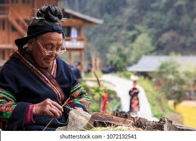 Langde, China - March 27, 2018: Old Miao woman weaving in Langde Miao village, Guizhou province, China