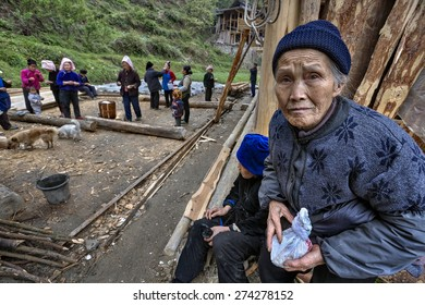 Langde Village, Guizhou, China - April 16, 2010: Miao people, , old Asian woman farmer, is sack boiled rice in his hands at  village festivities in honor of start of construction of a new farmhouse.