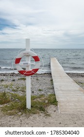 Langeland, Denmark - July 27th 2020: The characteristic red and white lifesaver from Tryg Fonden (Tryg Foundation) placed next to a jetty on the beach