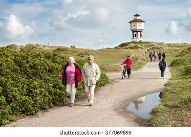 LANGEOOG, GERMANY - AUG 31, 2004: People walking in dunes and water tower of East Frisian island Langeoog, Lower Saxony