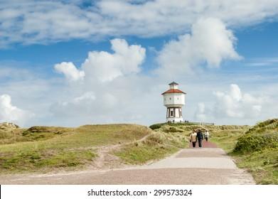 LANGEOOG ISLAND, GERMANY - AUGUST 31, 2004: People walking in dunes and water tower of East Frisian island Langeoog, Lower Saxony, Germany