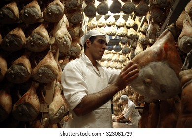 LANGHIRANO, ITALY - 25 SEPTEMBER 2014: An employee hangs on a rack hams greased with lard before moving them to dry in storage as part of the Parma ham curing process in Langhirano, Italy.