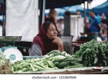 Langkawi island, Malaysia - December 9, 2018: Elderly woman greenery seller at the market. Unidentified local seller or Asian selling a vegetables, fruits and local produce on street market.