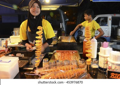 Langkawi island, Malaysia - January 13, 2016: Girl sale fried potatoes in the temporary night market
