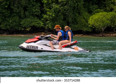 Langkawi, Malaysia - 2 February 2015 : Young man and girl on jet ski cruising mangrove river on February 2.