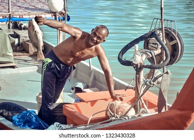 Langkawi, Malaysia - Dec 18: Asian fisherman with fish in hand. Hand holding fish. Hand holding fresh sea fish. Catcher shows fish to camera.