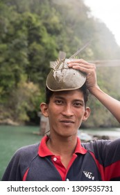 Langkawi, Malaysia - January 2, 2017: Funny portrait of tour guide with crab on his head from Kilim geo forest in Langkawi, Malaysia.