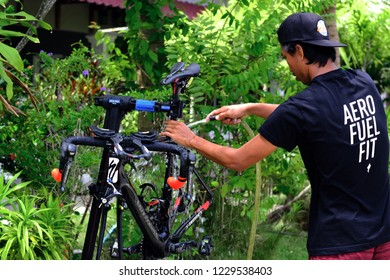 Langkawi, Malaysia - November 14, 2018: Asian man are washing road bicycle near by home. Preparing bicycle for triathlon race.