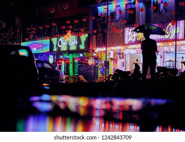 Langkawi, Malaysia - November 28, 2018: Colorful Asian cafes at rainy night and silhouette of man with umbrella. Night lights at restaurants area of the Bandar Kuah Town.