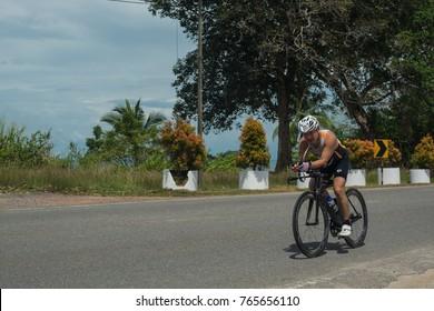 LANGKAWI, MALAYSIA-november 11: Sportsman rides a bike during the IRONMAN LANGKAWI triathlon on November  11, 2017 near Black Sand Beach, Langkawi Island, Malaysia.