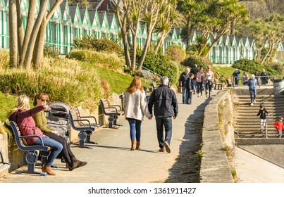 LANGLAND BAY, GOWER, WALES - FEBRUARY 2019: Man and woman walking hand in hand along the promenade in sunshine in Langland Bay on the Gower penninsula in Wales.