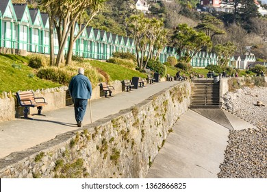 LANGLAND BAY, GOWER, WALES - FEBRUARY 2019: Person walking along the promenade in sunshine in Langland Bay on the Gower penninsula in Wales.
