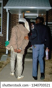 Langley Park, Maryland. March 12, 1988 Police officer walks the suspected crack  drug dealer into the police station in Hyattsville Md.