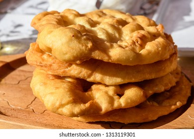Langos typical Hungarian food specialty, dish, deep fried dough on a wood table