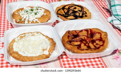 Langos, typical Hungarian food specialty, with sour cream, cheese, dill, chocolate syrup, jam on plastic plates for take away on a table, four deep fried donuts in direct sunlight at a food market