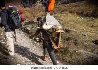 Langtang National Park / Nepal | April 10 2017: Unidentified sherpa carrying rocks on his back through the way at Langtang National park trekking in Himalayan mountains, Nepal