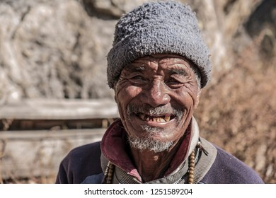 LANGTANG, NEPAL- NOVEMBER 08, 2018: Old nepalese man from Langtang valley with weathered face posing for the camera.